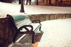 Winter park.green bench covered with snow in the Royalty Free Stock Images