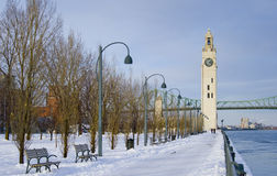 Winter park by river clock tower snow Montreal. Winter park with bench by river with snow lantern Montreal in afternoon light frozen cityscape Royalty Free Stock Photography