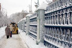 Winter pavement along wrought-. Pedestrians follow on the snow removal machine, that clearning pavement along high wrought-iron fence Royalty Free Stock Image
