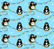 Winter penguin pattern. Winter penguin seamless pattern. Two cute penguins engaged in decoration with colorful Christmas lights on blue background with white Stock Photography