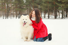 Winter and people concept - happy smiling young woman having fun with white Samoyed dog Stock Photos