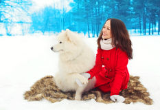 Winter and people concept - happy smiling young woman owner with white Samoyed dog Royalty Free Stock Photos