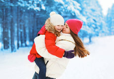Winter and people concept - positive mother and child having fun. In snowy day Stock Images