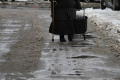 Winter. People are walking a snowy icy road after a heavy snowfall in the city, person with cane on an icy pathway, ice royalty free stock image