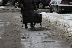 Winter. People are walking hard on a snowy icy road after a heavy snowfall in the city, person with cane on an icy pathway, ice Royalty Free Stock Photography