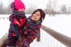 Winter photo of brunette ,daughter. Winter photo of brunette with daughter in park Royalty Free Stock Image