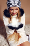 Winter photo of cute little girl with long blond hair wearing a hat ang gloves holding snow ball Stock Photo