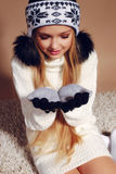 Winter photo of cute little girl with long blond hair wearing a hat and gloves Royalty Free Stock Images