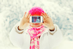 Winter photo hands woman taking photo self portrait on smartphone over snowy. Background Stock Image
