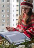A little girl in a knitted sweater sitting on a windowsill and reading a book. A winter photo of a little girl in a knitted sweater sitting on a windowsill and Royalty Free Stock Images