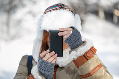 Winter photo. Women in winter clothing, fingerless mittens and ornamented hat with white fur photographing snowy landscape by a mobile phone. Shallow dof. Focus Stock Photography