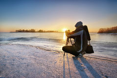 Winter photographer. On the ice at sunrise Royalty Free Stock Photo