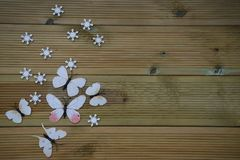 Winter photography image of white winter snowflakes and fun toy butterflies on rustic wood background and space. Taken in Chichester West Sussex. On the south Stock Photo