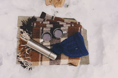 Winter picnic on the snow. Hot tea, thermos and snowball heart on cozy warm blanket. Outdoor seasonal activities Stock Photos