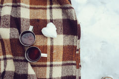 Winter picnic on the snow. Hot tea, thermos and snowball heart on cozy warm blanket. Outdoor seasonal activities Royalty Free Stock Photo