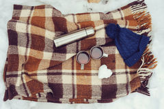 Winter picnic on the snow. Hot tea, thermos and snowball heart on cozy warm blanket. Outdoor seasonal activities Stock Photography