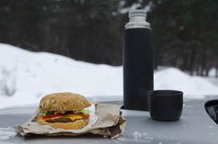 Winter picnic with tea and burger on the hood of a silver car against the background of the forest. Winter picnic with tea and burger on the hood of a silver car royalty free stock photo