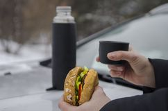 Winter picnic with tea and burger on the hood of a silver car against the background of the forest royalty free stock photography