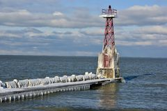 Iced Pier and Pier Light. This is a Winter picture of the iced pier and pier light at Foster Avenue Beach on Lake Michigan located in Chicago, Illinois in Cook stock photography