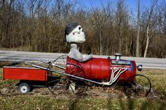 Halloween Art. This is a Winter picture of a piece of public art created for the Halloween Season of a skeleton driving a souped-up farm vehicle and wagon stock images