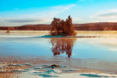 Winter picture of a small island. Beautiful winter picture on an island where the sky is reflected in a shiny ice Stock Photo