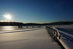 Winter pier frozen water at sunrise. Pier on frozen water on beautiful winter day at sunrise Stock Image