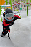 Winter play. Small boy rolls on street snow lump Royalty Free Stock Photos