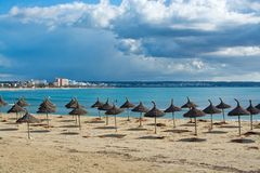 Winter Playa de Palma. PLAYA DE PALMA, MALLORCA, SPAIN - DECEMBER 16, 2017: Parasols on winter beach on a sunny day on December 16, 2017 in Mallorca, Balearic Royalty Free Stock Photography