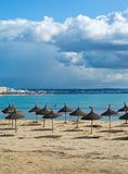 Winter Playa de Palma. PLAYA DE PALMA, MALLORCA, SPAIN - DECEMBER 16, 2017: Parasols on winter beach on a windy day on December 16, 2017 in Mallorca, Balearic Stock Images