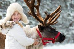 Winter playtime.Happy little girl hugging her reindeer. Royalty Free Stock Photos
