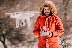 Winter-Porträt des Mannes warmes Jackenfliegenbrummen, steuerndes weißes quadcopter tragend stockbilder
