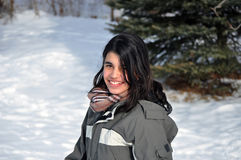 Pretty teenager girl going up a hill of snow while Stock Images