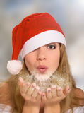 Winter portrait. Girl in a Christmas hat blowing snow royalty free stock image