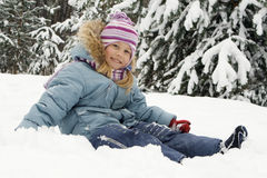 Winter portrait. The girl sits on snow Royalty Free Stock Photography