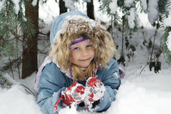Winter portrait. The girl lays in snow Stock Photography