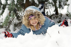 Winter portrait. The girl lays in snow, the happy child Royalty Free Stock Photo