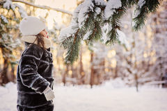 Winter portrait of adorable child girl blowing on snow on fir branch in forest Stock Image