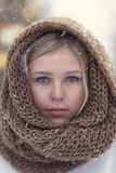 Winter portrait of attractive young blonde girl wearing knitted snood covered in snow. Stock Photography