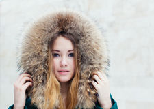 Winter portrait of beautiful girl in fur close-up. Toned in warm colors. Royalty Free Stock Image