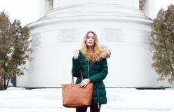 Winter portrait of a beautiful girl in a jacket with a fashionable bag Stock Images