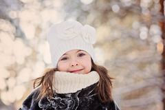 Winter portrait of beautiful smiling child girl in white hat. On the walk in sunny forest Stock Images