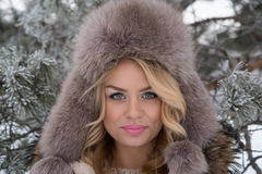 Winter portrait of beautiful smiling woman with snowflakes in white furs. Snow Stock Photo