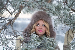 Winter portrait of beautiful smiling woman with snowflakes in white furs. Snow Royalty Free Stock Image