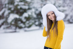 Winter portrait of beautiful smiling woman with snowflakes in white furs Stock Photo