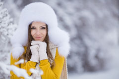 Winter portrait of beautiful smiling woman with snowflakes in white furs. Beautiful winter portrait of young woman in the winter snowy scenery Stock Image