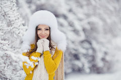 Winter portrait of beautiful smiling woman with snowflakes in white furs. Beautiful winter portrait of young woman in the winter snowy scenery Royalty Free Stock Photos