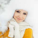 Winter portrait of beautiful smiling woman with snowflakes in white furs Royalty Free Stock Photo