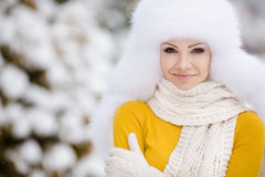 Winter portrait of beautiful smiling woman with snowflakes in white furs Royalty Free Stock Photography