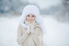 Winter portrait of beautiful smiling woman with snowflakes in white furs Royalty Free Stock Images