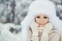 Winter portrait of beautiful smiling woman with snowflakes in white furs. Beautiful winter portrait of young woman in the winter snowy scenery Royalty Free Stock Images